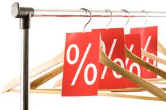 close-up of hangers with red labels showing percentage in shop - stock photo