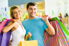 Happy man with paperbags in hand touching his girlfriend while in the shopping m Stock Photos