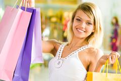 Portrait of blond girl holding shopping bags in hands and looking at camera with Stock Photos