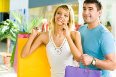 Portrait of happy couple standing in the shopping centre with bags while choosin Stock Photos