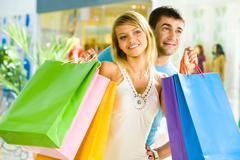 Muotokuva hymyilevä mies käsittää nuori nainen, jolla ostoskassit Kuvituskuvat