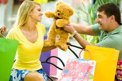 Portrait of happy man giving a teddy-bear to her girlfriend in the shop Stock Photos