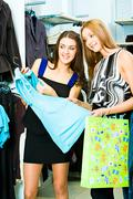 portrait of two friends in the shopping centre standing in the clothing departme - stock photo