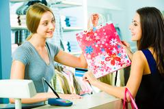 photo of a friendly salesperson giving shopping bag to pretty customer in the ma - stock photo