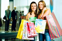 Stock Photo of portrait of two smiling girls wearing casual clothes with paper bags in their ha