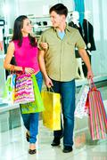 Photo of a young modern couple going shopping in the shopping mall carrying bags Stock Photos