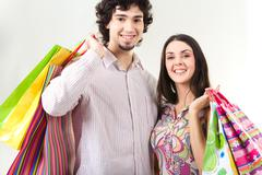 portrait of young people holding bags and looking at camera - stock photo