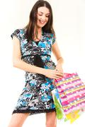 portrait of a young smiling woman with bags in hands - stock photo