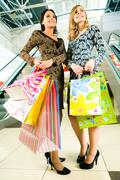 Portrait of two friends with shopping bags in hands standing in the centre Stock Photos