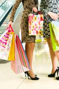 View of ladies' hands holding bags standing in the shopping centre Stock Photos