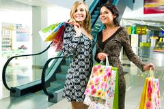 Image of young ladies looking at something with admiration in the shopping centr Stock Photos
