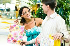 Image of beautiful girl looking happily at young man and laughing in the store Stock Photos