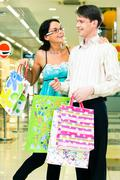 photo of man standing in the shopping mall with bags in hands while beautiful wo - stock photo