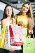 Vertical image of happy girls carrying colorful bags in hands and looking at cam Stock Photos