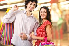 image of two young people in the shopping mall looking at camera - stock photo