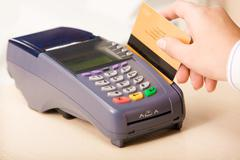 close-up of human hand putting credit card into payment machine in shopping cent - stock photo