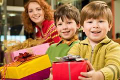 Cute youngster holding and giving nice christmas present looking with smile Stock Photos
