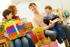 portrait of cheerful couple and their two sons sitting in supermarket with prese - stock photo