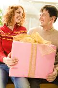 Portrait of smiling couple holding big pink gift box and looking at each other Stock Photos