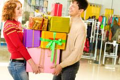 portrait of shopaholics holding heap of presents and wondering what to do next - stock photo