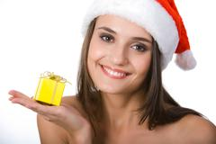 face of happy woman wearing santa cap and small yellow giftbox on palm - stock photo