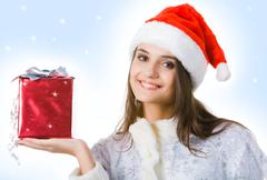 portrait of smiling snow girl holding present in hand and looking at camera - stock photo