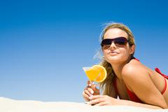 Portrait of relaxing woman wearing sunglasses with glass of cocktail in hand lyi Stock Photos