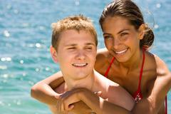 Close-up of smiling girl hugging her boyfriend on the background of blue sea dur Stock Photos