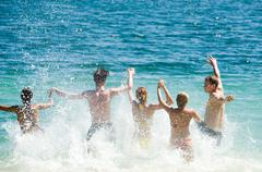 portrait of five young people running in the lake all together - stock photo