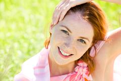 portrait of redheaded woman with freckles touching her head - stock photo