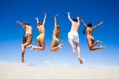 Portrait of jumping young people a backs on the beach Stock Photos