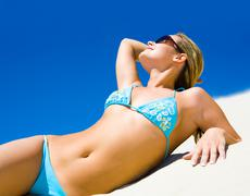 Portrait of young woman with sunglasses lying on the sand and enjoying by sun Stock Photos
