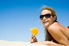 portrait of charming woman with orange cocktail and sunglasses on the background - stock photo