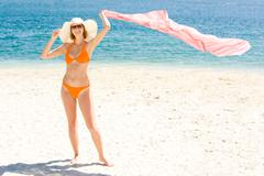 Photo of cheerful woman standing on the beach with pareo in hand Stock Photos