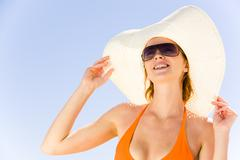 Stock Photo of close-up of pretty girl in hat and sunglasses on the background of blue sky