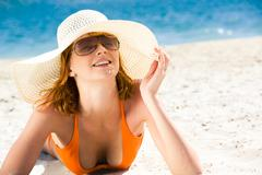 Portrait of happy woman lying on the seashore and sunbathing Stock Photos