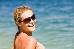 portrait of happy girl wearing sunglasses looking at camera and laughing by the - stock photo