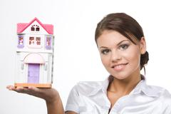 Portrait of young woman holding toy house on a white background Stock Photos