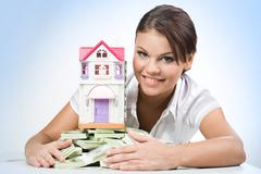 portrait of beautiful woman touching heap of money with toy house on its top - stock photo