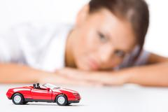 Stock Photo of red toy car on background of woman looking at it