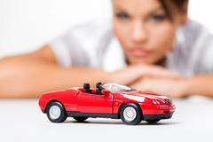 close-up of a toy car with thinking woman at background - stock photo