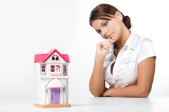 Image of miniature toy house with pensive female at background Stock Photos
