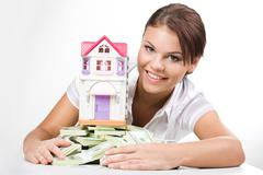 portrait of lucky woman raking up heap of money with toy house on its top - stock photo