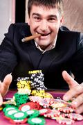 portrait of rich man raking up chips in the casino - stock photo