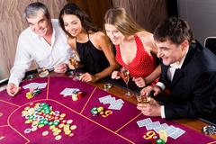 Portrait of people sitting at the table and gambling Stock Photos
