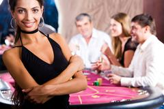 portrait of fashion woman in black dress in the casino - stock photo