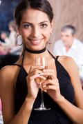 Portrait of fashionable woman with glass of champagne in hands looking at camera Stock Photos
