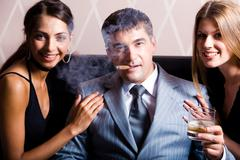 portrait of successful man smoking a cigar holding whisky with pretty women near - stock photo