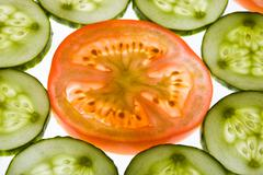 close-up of tomato slice surrounded by cucumbers - stock photo