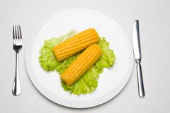 two ears of corn placed on the plate with fork and knife near by - stock photo